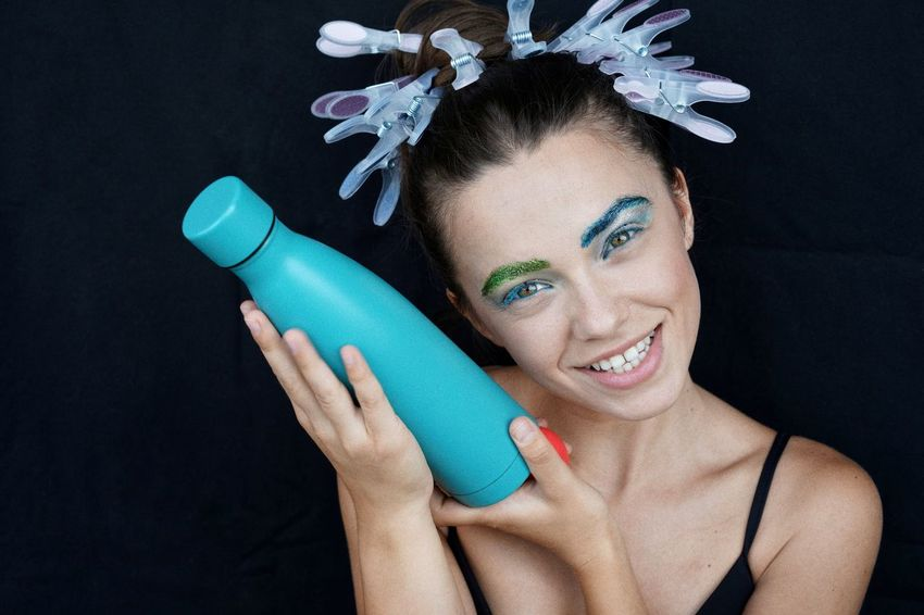Portrait of a bottle. Holding A Bottle Bottle Blue Portrait Smiling Smile One Woman Only One Young Woman Only People One Person Holding Human Hand Black Background Beauty Studio Shot Fashion Model Beautiful People Young Women Stage Make-up Ceremonial Make-up Eye Make-up Beauty Product Body Paint Eyeshadow Mascara The Portraitist - 2018 EyeEm Awards The Still Life Photographer - 2018 EyeEm Awards