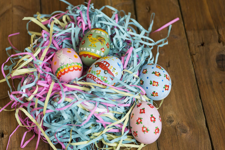 Painted eggs lie in a basket, wooden background, easter Close-up Day Easter Food Food And Drink Freshness High Angle View Indoors  Multi Colored No People Ribbon Table