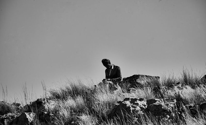 Man sitting on rock at field against clear sky