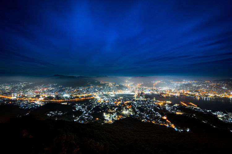 Aerial View Of Illuminated City Against Dramatic Sky At Night