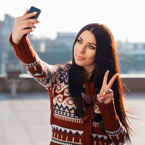 Portrait of beautiful young woman using mobile phone
