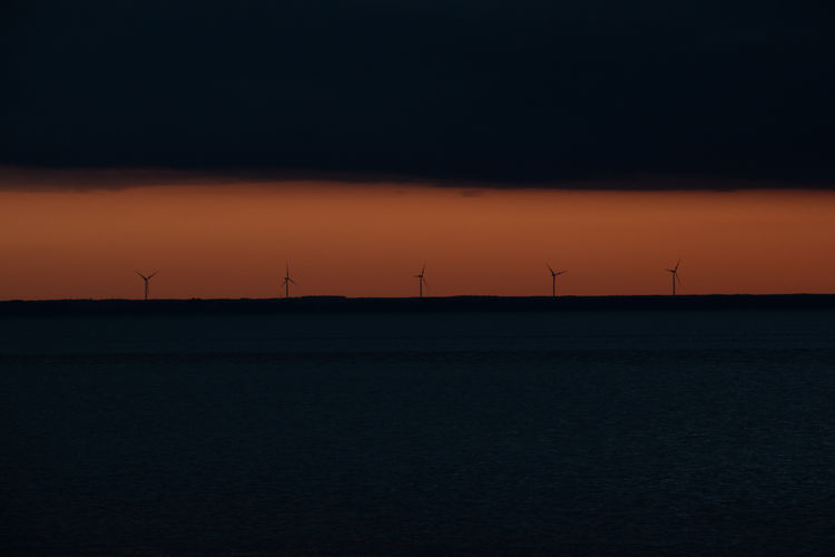 Silhouette windmills on land against sky during sunset