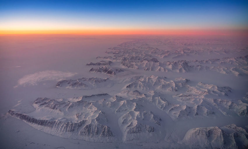 Aerial view of snowcapped landscape against sky during sunset