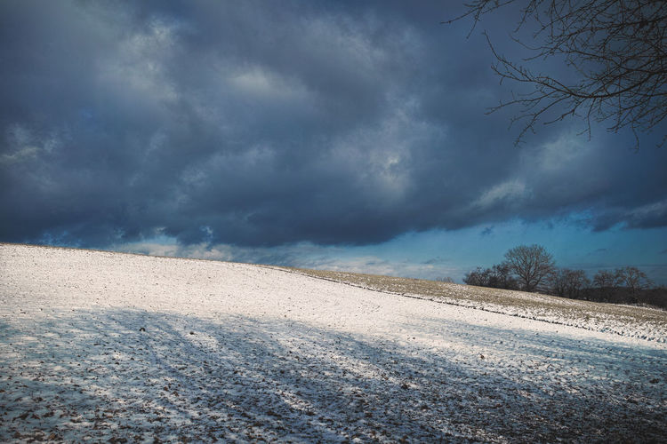 Road on field against sky during winter