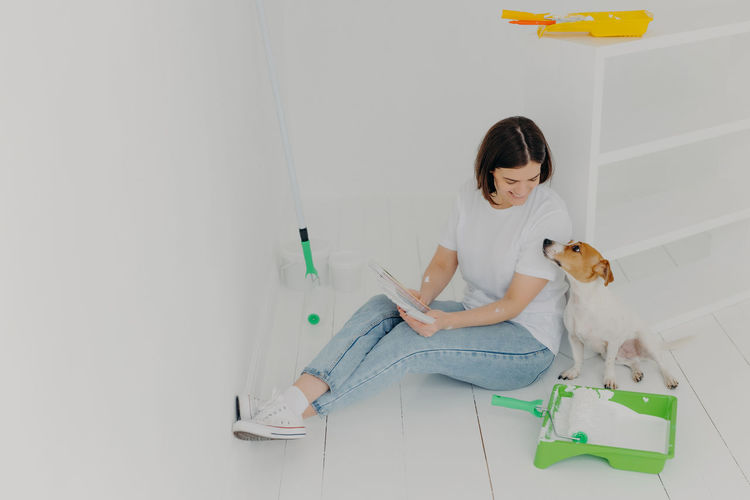 Woman with dog sitting on floor against wall at home