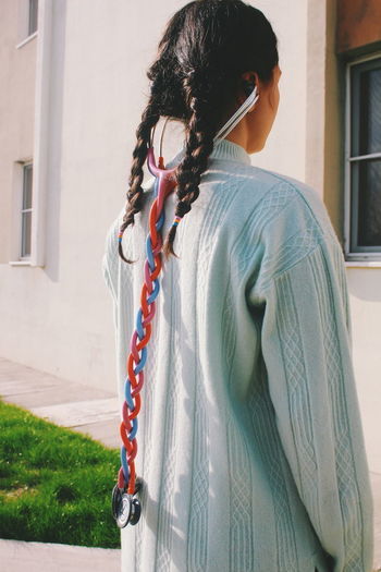 Rear View Of Woman With Braided Hair And Stethoscope Outdoors