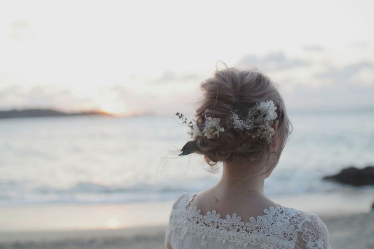 Rear view of bride wearing flowers at beach