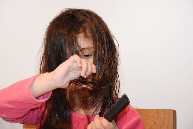 Girl combing hair against wall at home