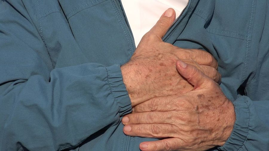 Midsection of man touching chest