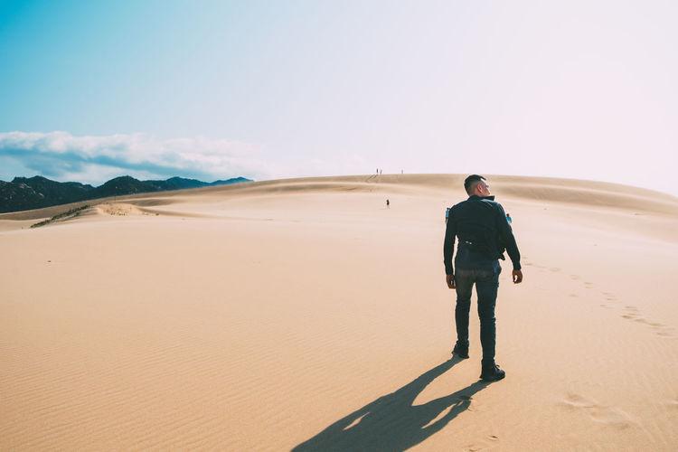 Full length of man standing on sand dune