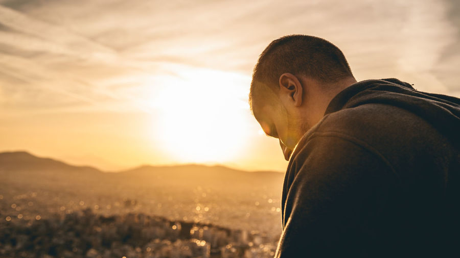 Side view portrait of young man standing against sky during sunset