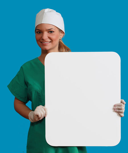 Young woman doctor keeping a white board, against a blue background. Copy Space Doctor  Healthcare Medicine Nurse White Board Adults Only Blue Blue Background Communication Front View Happiness Holding Keeping Looking At Camera Medical Cannabis Message Occupation One Person People Physician Smiling Studio Shot Young Adult Young Women