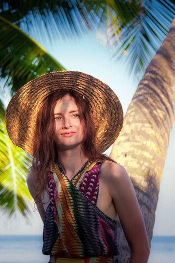 Young woman wearing hat standing by tree trunk at beach