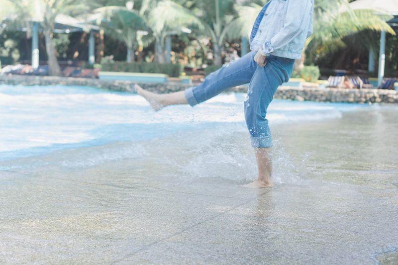Low section of man splashing water at swimming pool