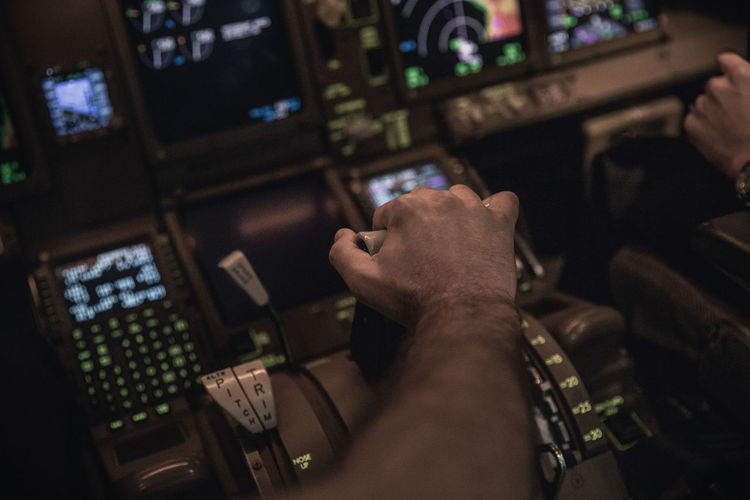 Cropped hand of pilot holding gear in airplane