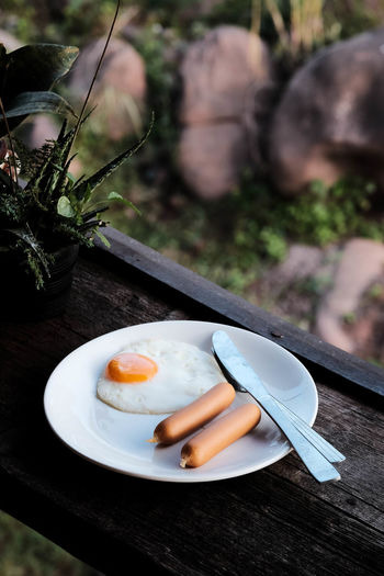 American breakfast with eggs and sausage put on white plate with knife , wood background.
