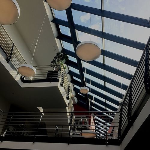 Low angle view of illuminated lamp hanging on ceiling in building