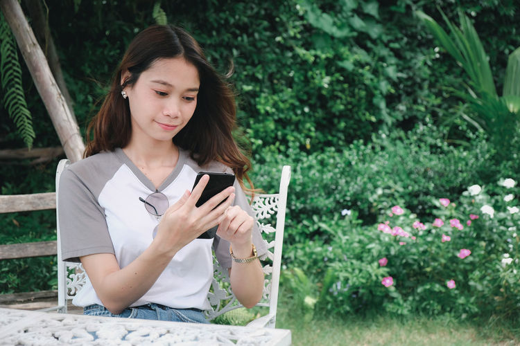 Young woman using mobile phone while sitting on plants