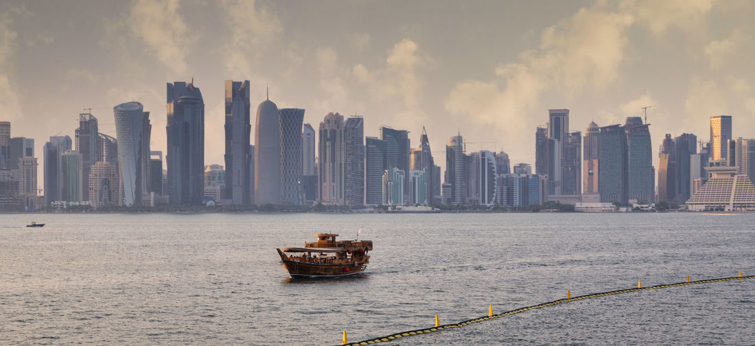 Nautical vessel on sea against buildings in city