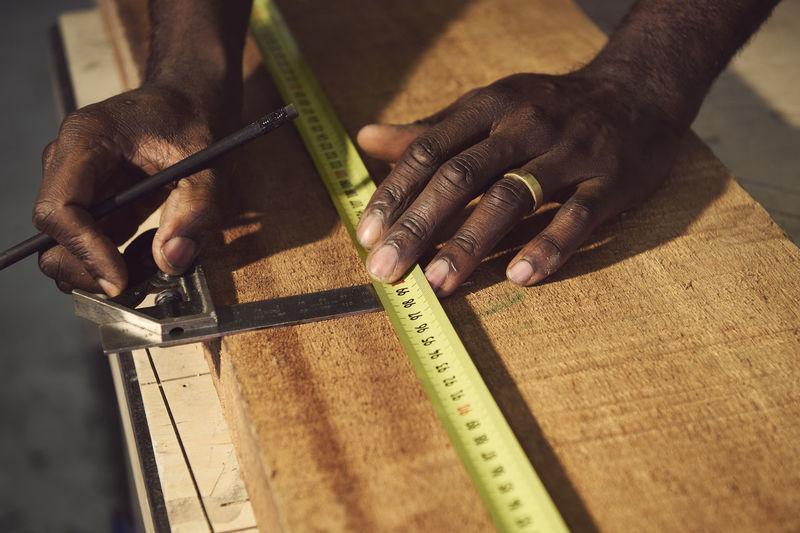 Cropped hands of carpenter working at workshop