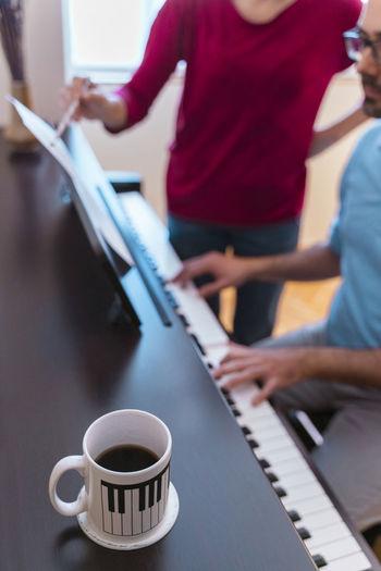 Man and woman using piano at home
