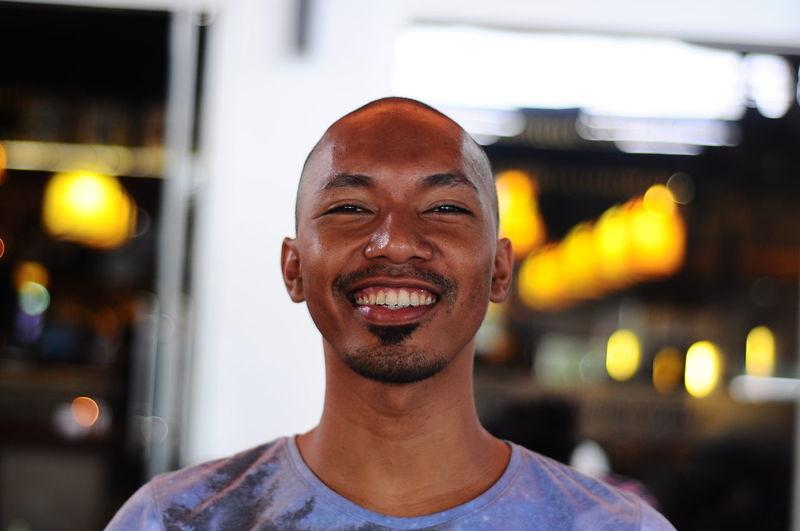 Portrait Of Smiling Man Against Illuminated Lighting Equipment