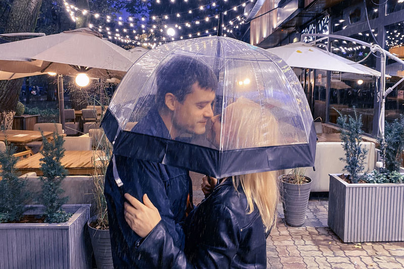 Romantic couple man and woman under an umbrella in the rain on the background of a street cafe.