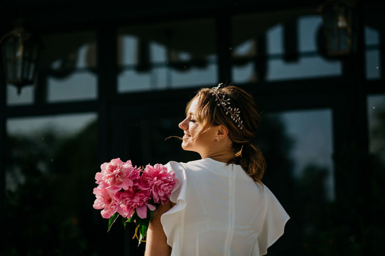 Rear view of woman standing by pink flowering plants