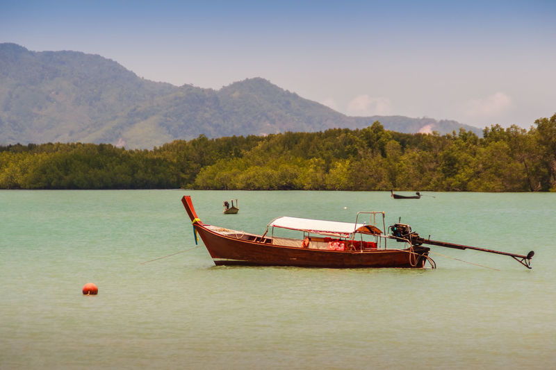 Fisherman boat and the Beautiful seascape view with blue sky and mountain on background at Phuket, Thailand Mountain View Beauty In Nature Blue Sky Blue Skys Day Fisherman Boat Lake Mode Of Transport Moored Mountain Mountains And Sky Nature Nautical Vessel No People Outdoors Scenics Seascape Seascape Skyscape Sky Tranquil Scene Tranquility Transportation Tree Water