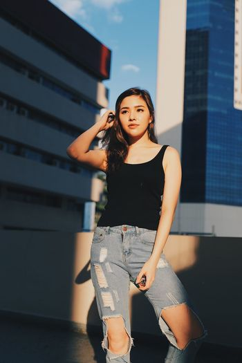 Young woman wearing torn jeans looking away standing against building on terrace