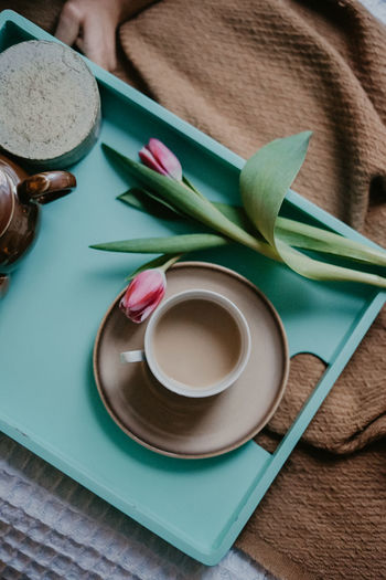 High angle view of coffee cup and tulip in tray on table