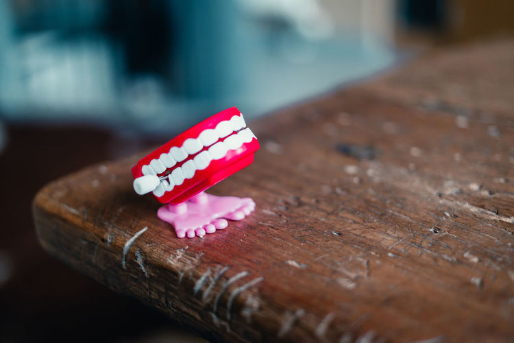 Close-up of red artificial denture on table
