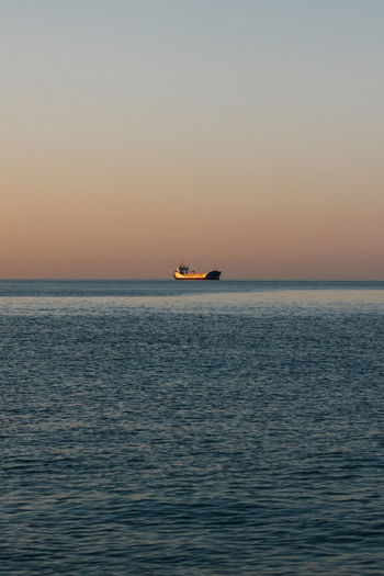 Scenic view of boat sailing in sea against clear sky