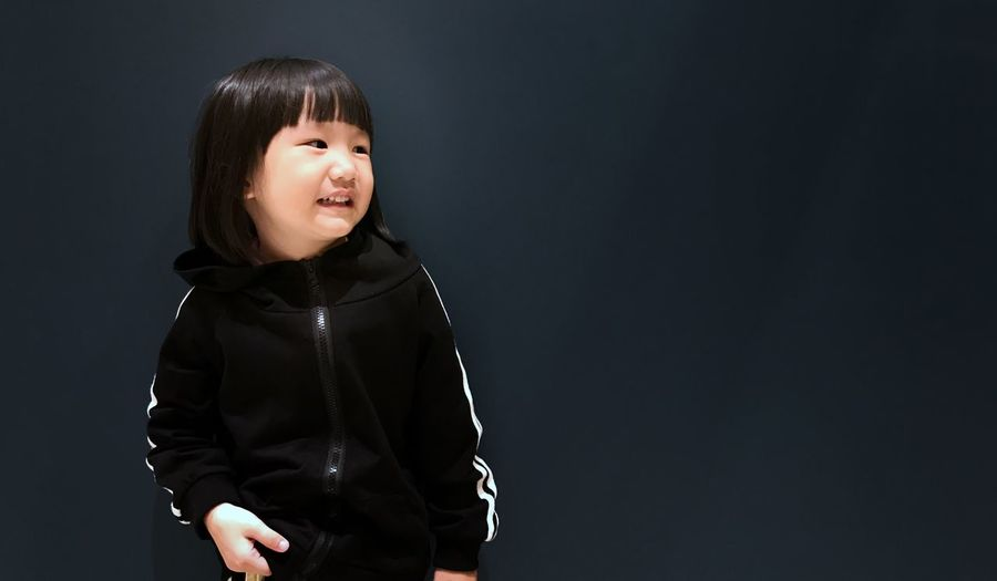 EyeEm Selects daughter with children's sportswear on dark background Studio Shot One Person Waist Up Childhood Real People Standing Lifestyles Black Background Bangs Looking At Camera Indoors  Portrait Close-up Day People