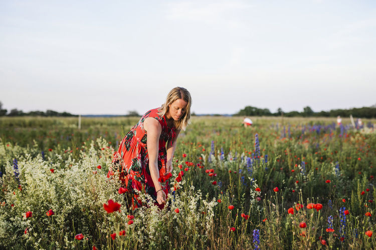 Full length of young woman on poppy field against sky