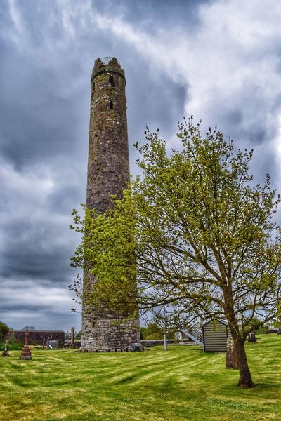 Kildare Round Tower Tower Sky Architecture Monument History Cloud - Sky Outdoors Ancient Old Ruin Irishlandscape Dark Clouds Tree Sky_collection Quiet Moments Tranquility Irelandinspires Landscape Ireland Kildare Cathedral Round Tower Low Angle View Irish Countryside Day
