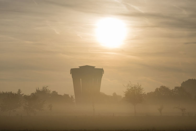 Beauty In Nature Day Nature No People Outdoors Silhouette Sky Storage Tank Sun Sunbeam Sunlight Sunrise Sunshine Tree Water Tower - Storage Tank