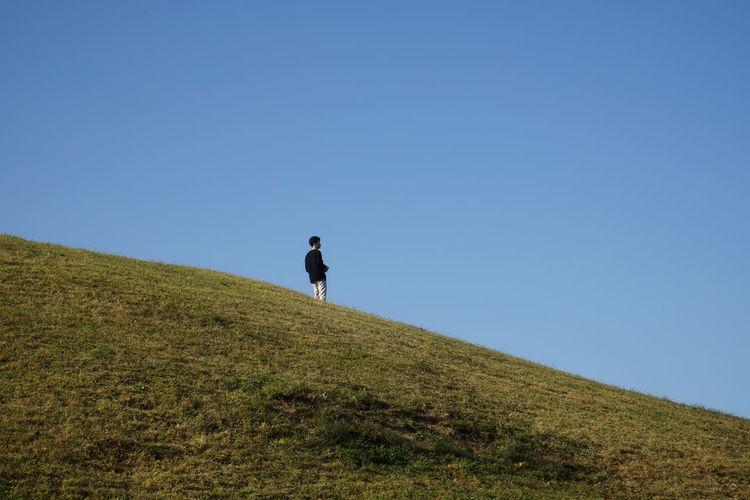 Man walking on field against clear blue sky