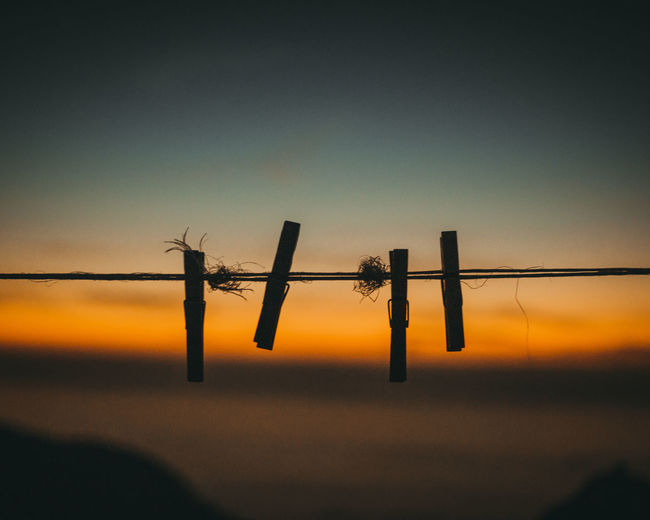 Silhouette of barbed wire fence against sky during sunset