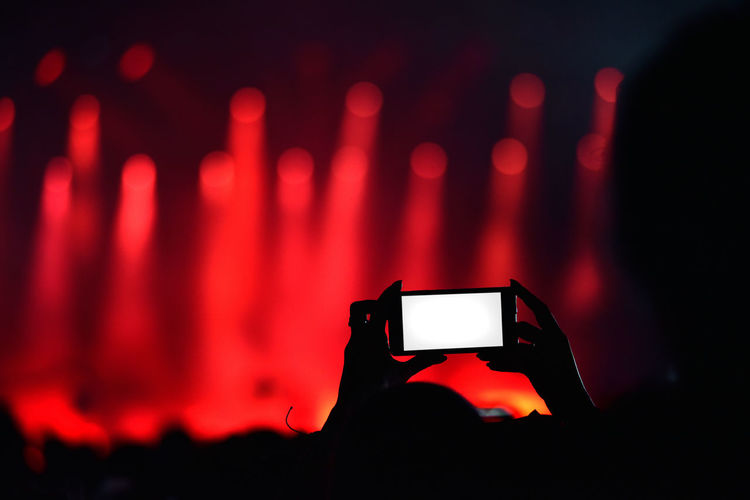 Close-Up Of Hand Photographing With Smart Phone During Concert