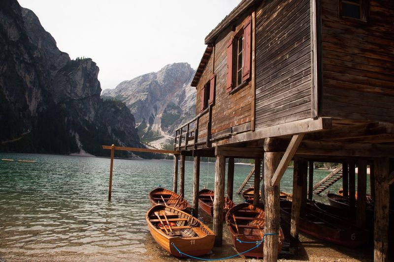 Boats moored below stilt house in lake against mountains