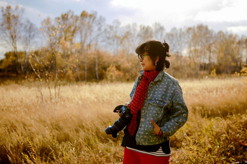 Woman holding camera looking away while standing on land