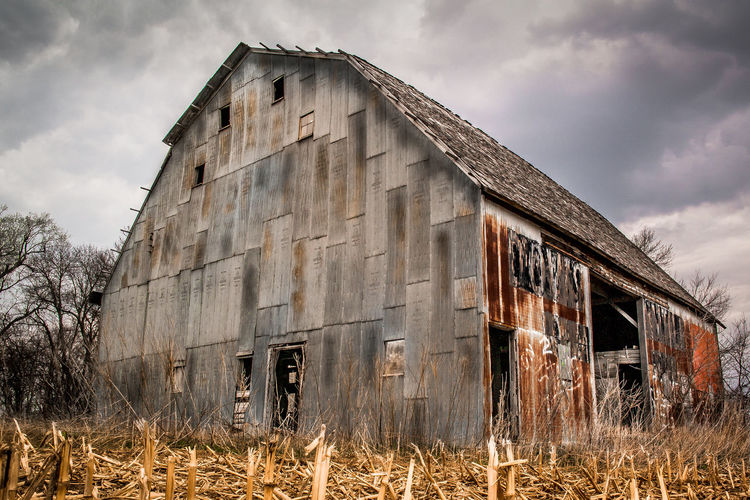 View of abandoned barn against cloudy sky