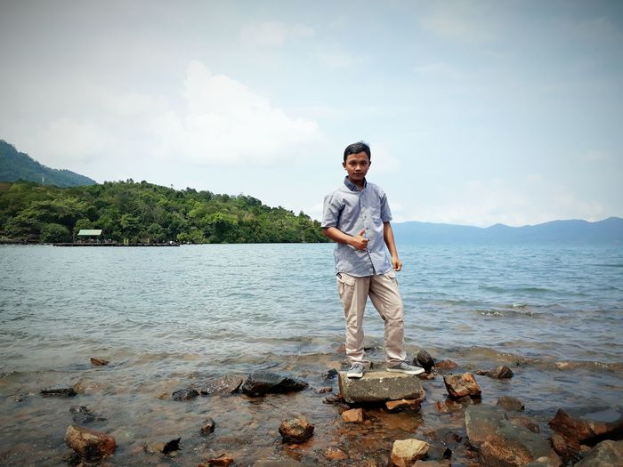 Young man standing on rock amidst sea against sky
