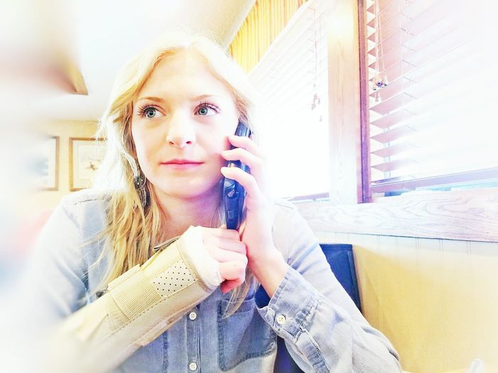 Woman talking on phone while sitting at restaurant