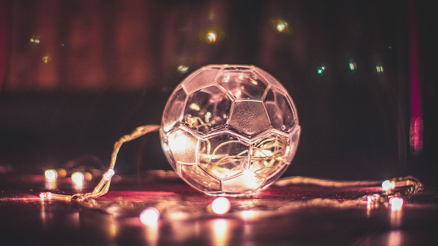 Close-up of illuminated glass ball on table