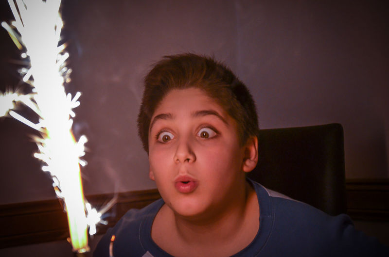 Cute boy blowing sparkler at home
