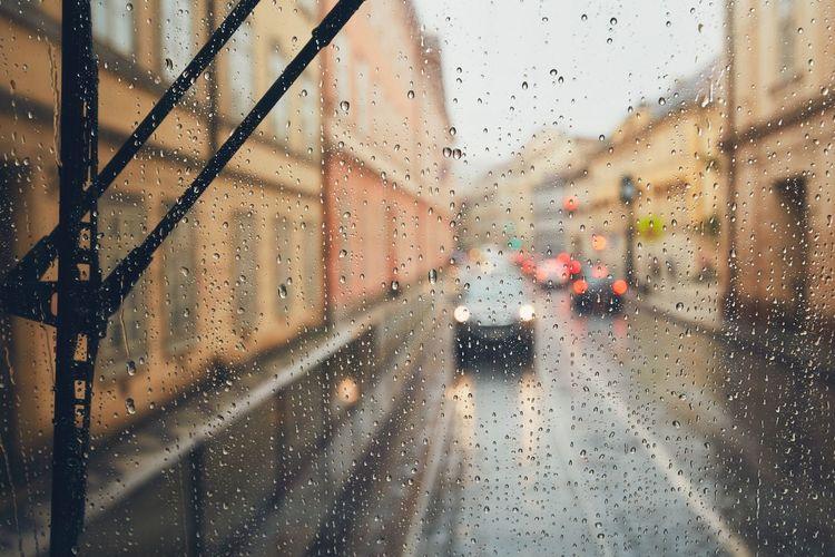 Car on street seen through wet glass window