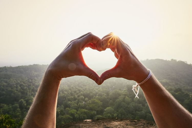 Close-Up of hands making heart shape against landscape at sunset. Outdoors Young Men Romantic Copy Space Landscape Forest Vacations Travel Sun Sunset Close-up Personal Perspective Love Emotion Making Positive Emotion Nature Lifestyles One Person Human Body Part Sky Real People Heart Shape Human Hand Hand