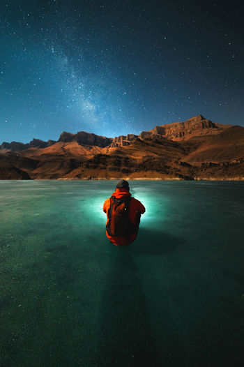 Man sitting on mountain against sky at night